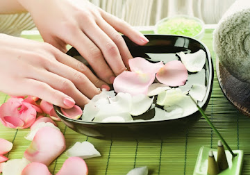 Lady dipping nails in rose water