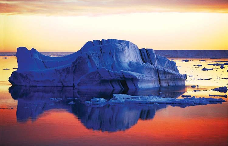 A tabular iceberg in Antarctica at sunset, seen during a Lindblad Expeditions tour.