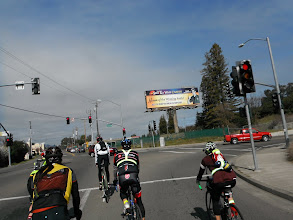 Photo: Cyclist  pedal past an ad for the Sho Ka Wah Casino