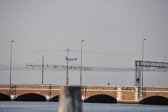 Photo: Most Svobody je silniční most, který spojuje města Benátky a Mestre. Navržen byl v roce 1931 a otevřel ho Benito Mussolini v roce 1933 jako Ponte Littorio. Most je jedinou silnicí vedoucí do Benátek. Na konci druhé světové války byl přejmenován na počest konce fašistické diktatury. Je 3,85 km dlouhý a má dva jízdní pruhy v každém směru. Na mostě nejsou odstavné pruhy. Je postaven podél železničního mostu, který byl postaven v roce 1846 a je stále v provozu.