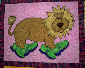 Photo: The lion is walking proudly in his green shoes. Bernadine hand appliqued around all the animal blocks and machine quilted the background using designs from the quilt.  In this block she appliqued flowers and hearts to match the lion's tail..