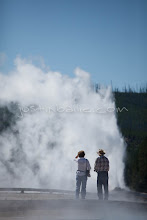 Photo: Two people watching Old Faithful Geyser in Yellowstone National Park, WY.