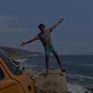 Man posing on rock overlooking the ocean