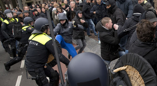 Dutch riot police wield their batons as they disperse a group of people during pro and anti immigrations rallies in Amsterdam, Netherlands, Saturday, Feb. 6, 2016. Thousands of people took part in protests against Islam and immigration in several European cities. (AP Photo/Peter Dejong)