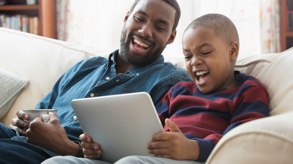 Father and son laughing looking together at a tablet