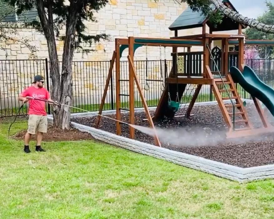 A man pressure washing a swing set