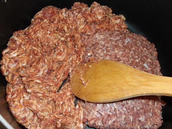 While sauce is cooking, add sweet Italian sausage and ground beef to a large...