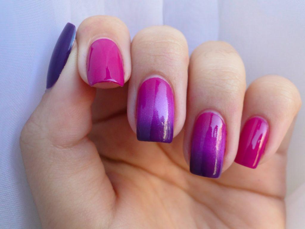 Mão com unhas pintadas em tons degradê de roxo e rosa. Foto: Site Hair Address. Post: Nail art fáceis para fazer em casa