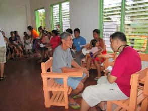 Photo: Dr. Gene Nisperos talks to an elderly patient