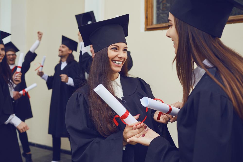 Shutterstock_1677330001 Female graduates with diplomas hugging laugh