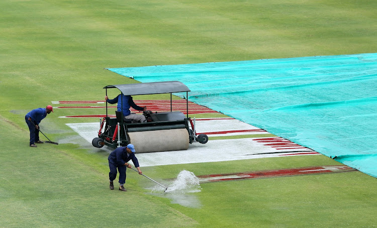 Ground staff workers are seen as they try to sweep water on the pitch after play was delayed due to rain.
