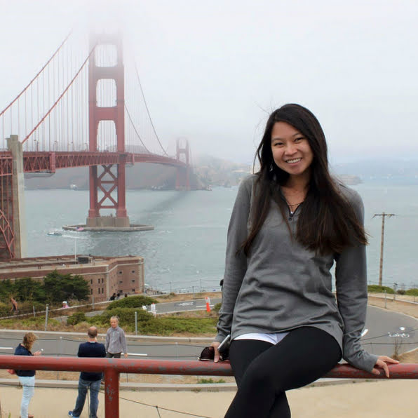 Woman smiling in front of the Golden Gate Bridge.