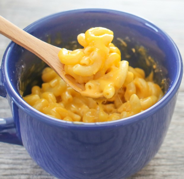 Macaroni and cheese in blue mug with wood spoon