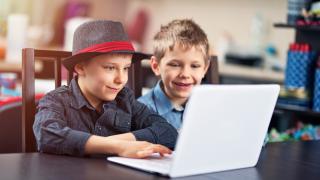 dos niños mirando un portátil
