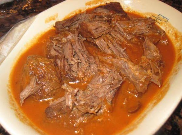 After your pot roast has cooled a bit, remove from saucepan and shred it...