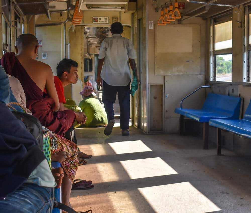 monk and other people in burma train