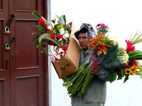 Photo: Vendor, late to market,  carrying his entire stock in trade in his arms