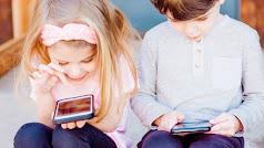 Dos niños pequeños juegan con el móvil de sus padres.