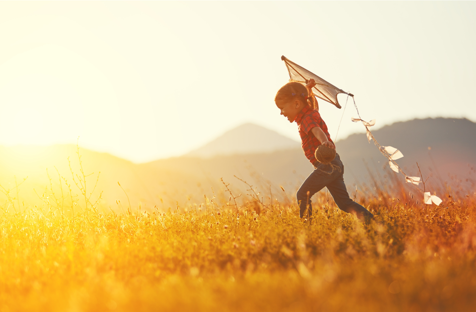 Child playing outside with a kite to help reduce myopia