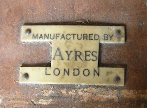 """Photo: Ayres' name-plate from a rocking horse stand of late 1940's. Note the odd cut-out : it produces a stylised """"H"""", but is that the reason? It could - for some reason - be to remove the """"FH"""" and """"Ltd"""". By this date, Ayres had been taken over (by Slazenger), so it may have been done to use up old-stock plates.  As may be seen elsewhere on my Picasa site, another chess-manufacturer - HP Gibson & Son Ltd - was effectively shut down, for the duration of the war, in 1940 after a severe bombing raid on London destroyed their premises and equipment. That firm's premises  were situated at 101 Aldersgate Street, London  - just 'down the road' from FH Ayres at no.111 Aldersgate Street. Although I have seen no specfic confirmation of this, it seems reasonable to speculate that the same bombing raid had a serious effect on the Ayres business, possibly forcing it to seek a 'white knight' partner to take it over."""
