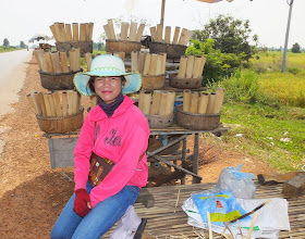 Photo: This lady fills the bamboo containers with rice, beans and coconut milk and cooks over coals.