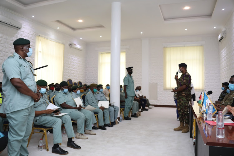 A KDF officer speaks to Mombasa county Inspectorate officers during the graduation ceremony