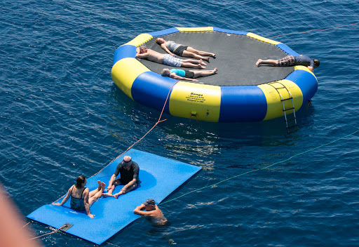 wind-surf-float.jpg - Passengers relax on a sunny afternoon on a giant ocean float at the rear of Wind Surf.