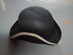 Photo: Let the hat dry completely, about 24 hours.  Glue your trim of choice all the way around the edge of the brim.  (Start and finish gluing on the side where you plan to add your decoration.)  Let the glue dry.