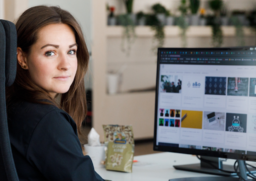 a woman operating a computer looking at the camera