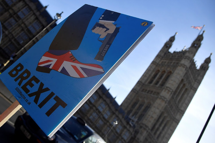 A demonstrator holds a placard during an anti-Brexit protest opposite the Houses of Parliament in London, Britain, December 17 2018. Picture: REUTERS/TOBY MELVILLE