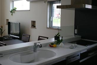 Photo: キッチン・カップボードと同色のキッチンパネルにも注目。