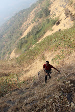 Photo: Sunny Jamshedji watching intently as Richie Kher climbs his first aid pitch. It was hairy walking on these steep, slippery, grass-covered slopes with the valley 1,500' below the pinnacles. (Courtesy Ajit Bobhate)