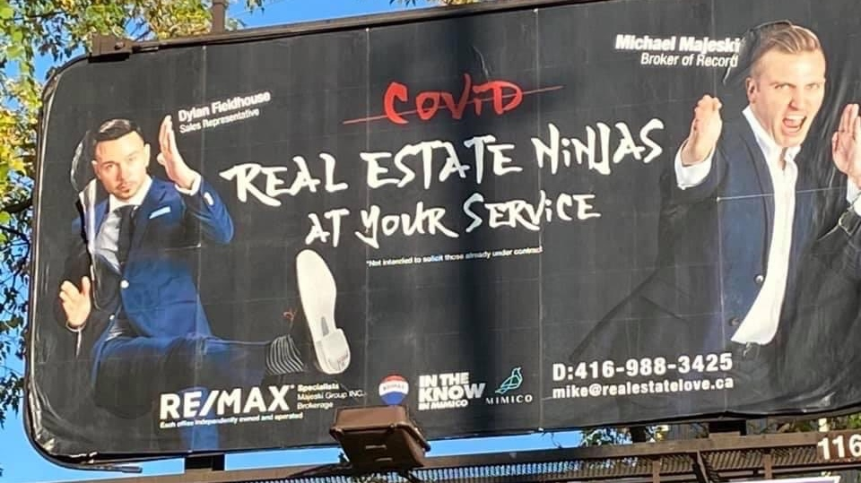 "A REMAX billboard with two men doing karate poses and the word Covid crossed out and the text ""Real Estate Ninjas at your services."""