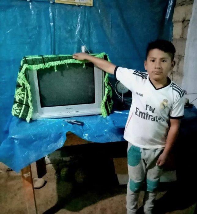 Niño parado al lado de una televisión