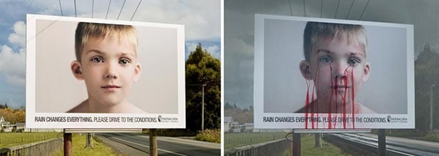 "Two billboards on the highway, one with a young boy's face saying ""Rain changes everything. Please drive to the conditions."", and the other one is the same billboard but it is raining outside and the boy has blood coming out of his nose and eyes."