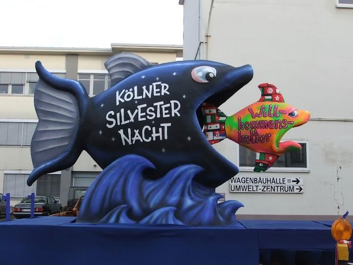 Großer dunkler Fisch «Kölner Silvester Nacht» schluckt kleinen bunten «Willkommenskultur».