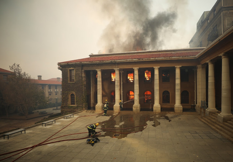 Firefighters battle flames engulfing the University of Cape Town library and the Special Collections library on Sunday. The runaway blaze, which started on Table Mountain, also engulfed the Rhodes Memorial restaurant and Mostert Mill, which was built in 1796 and was the oldest surviving working windmill in SA. Picture: MIKE HUTCHINGS/REUTERS