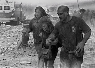 Photo: Survivors run for cover following the destruction left in the wake of the 9/11 attacks.