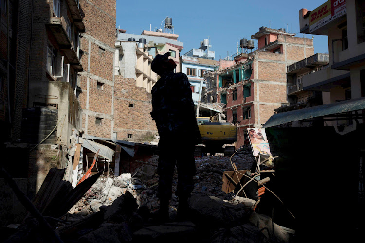 A policeman stands guard at a site of collapsed buildings as rescue workers clear debris after an earthquake in Kathmandu, Nepal. Picture: REUTERS
