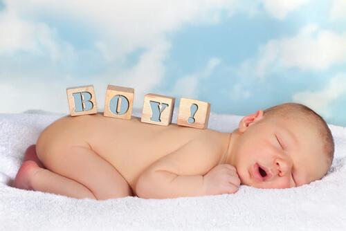 タオルの上で気持ちよさそうに眠っている男の子の赤ちゃん