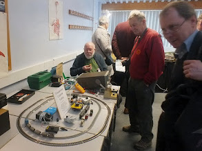 """Photo: 137 Greenwich & District NG Society member Richard Glover laid on a testing station, complete with oscilloscope and a comprehensive variety of typical controllers used by narrow gauge modellers so that comparison tests could be made of loco performances on both 9 and 16.5mm gauge tracks with different controllers of pulse, feedback, variable voltage and even """"vintage"""" variable resistance configurations. As expected, results were inconclusive, but it was fun! Paying full attention here are 009 esteemed """"elders"""" Phil Savage in the maroon Sussex Downs shirt and previous 009 Society Chairman David Burleigh ."""