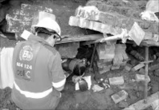 TRAPPED: A member of the emergency rescue services tries to remove one of the two construction workers who were trapped under rubble when a wall of a building collapsed in Merewent, south of Durban. Pic. ER24.