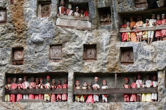 Photo: Lemo Tana Toraja (Sulawesi)   Siguiendo la tradición toraja, este cementerio es una pared de piedra en la que se han excavado –en horizontal- las tumbas. Hay balcones desde los que vigilan los tau-tau, que son estatuas hechas de madera o bambú a imagen de los difuntos ahí enterrados. La palabra ¨tau¨ en toraja quiere decir hombre, y ¨tau tau¨ quiere decir ¨hombres¨ o ¨estatuas¨. Desde su posición tienen una buena vista de los campos de arroz que hay enfrente. Paseando por la zona pasamos por un par de tiendas artesanales donde además de vender recuerdos había dos artesanos haciendo estas figuras.  Lunes 23 de marzo de 2015