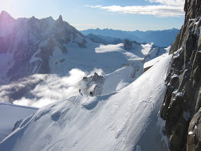 "Photo: Climbers descend a snow-covered ridge leading down from the Aiguille du Midi. (Aiguille means ""needle"")"
