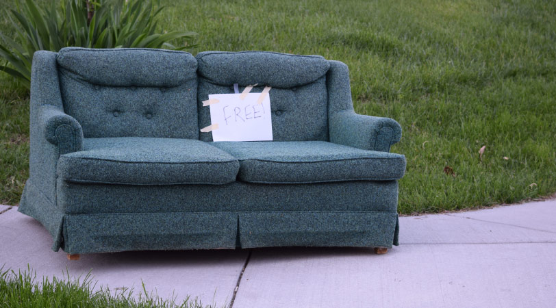 """A couch outside with a paper sign that says """"FREE"""" on it"""