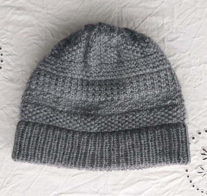 A grey handknit hat with textured stitch pattern and long folded brim.