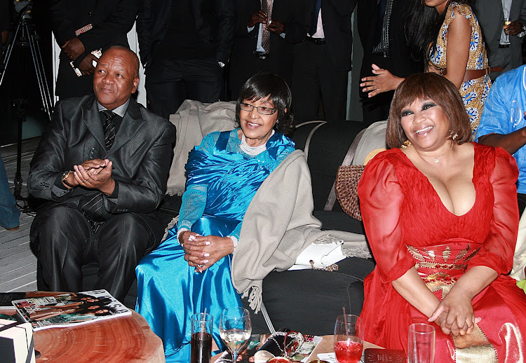 Former justice minister Jeff Radebe, Winnie Madikizela-Mandela and birthday girl Zindzi Mandela view a slide show of family pictures at her 50th birthday party at Randlords nightclub in Braamfontein on January 15 2011.