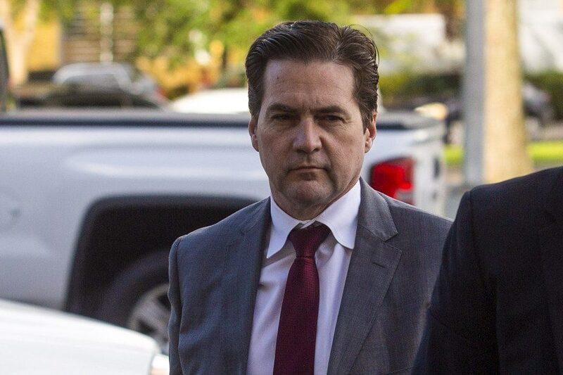Craig Wright en costume gris, cravate rouge cheveux gominés et le regard fuyant.