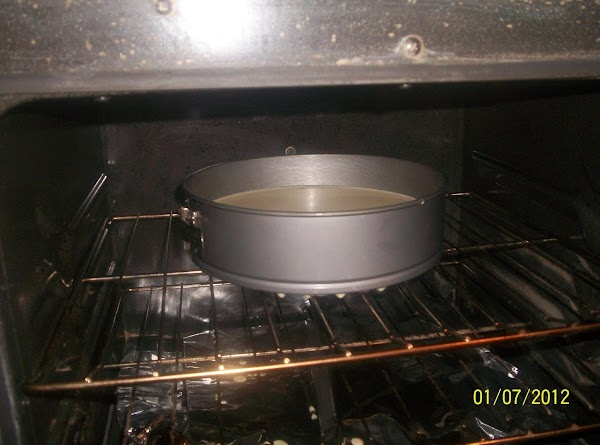 Place the springform pan in a large roasting pan.Pour hot water into the roasting...