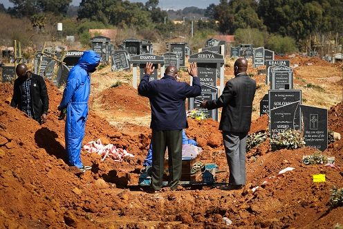 Family members gather to bury a loved one at Cambrian Cemetery in Ekurhuleni on Tuesday.